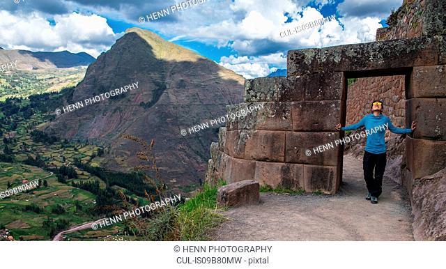 Woman exploring Inca ruins above Ollantaytambo, Peru