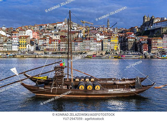 Sandeman and Porto Cruz Port wine boats called Rabelo Boats on a Douro River in Vila Nova de Gaia city. Porto city river bank on background