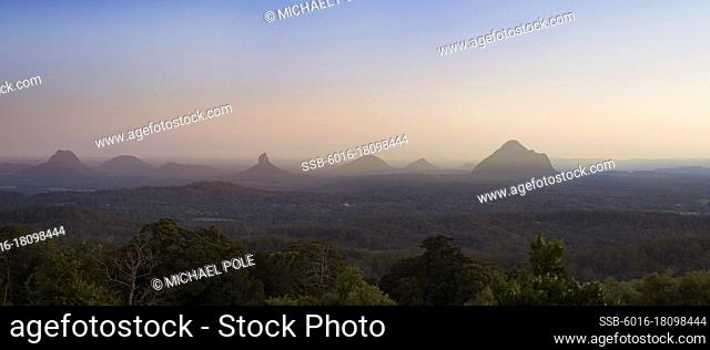 Looking over native bushland towards Glasshouse Mountains at sunset