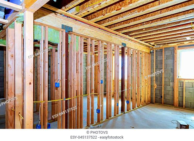 Frame of a wall and a ceiling of a wooden house, vapor barrier, partially sheathed walls installation in the basement