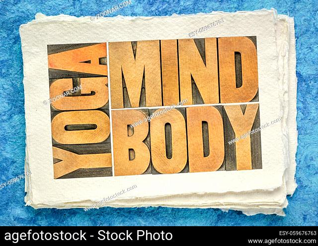 yoga, mind, body word abstract - text in letterpress wood type on handmade paper, meditation, wellness and lifestyle concept