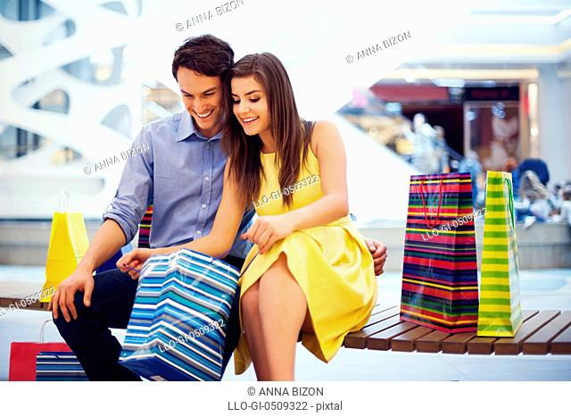 Happy couple peeking into shopping bag Debica, Poland