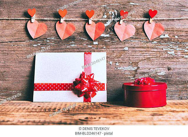 Valentine hearts hanging on string above gift box and card
