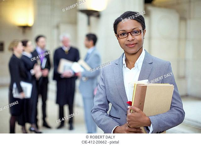 Lawyer standing with documents in courthouse