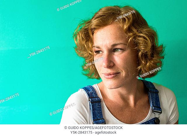Tilburg, Netherlands. Studio portrait of a redheaded caucasian woman in front of a green background