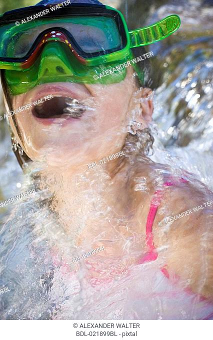 young girl in water wearing diving goggles