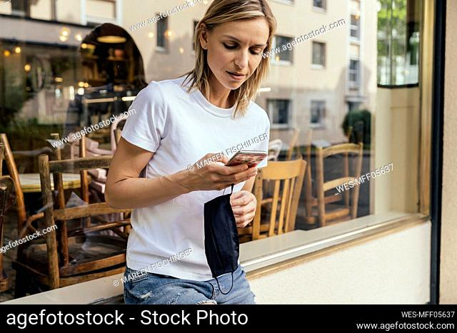 Woman with protective mask in her hand looking at smartphone in front of a closed coffee shop