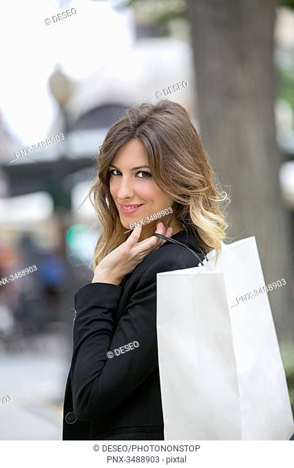 Pretty blonde woman with shopping bags in downtown