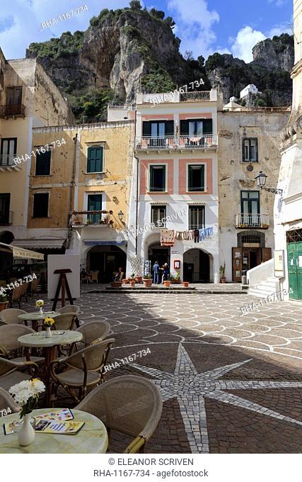Town square with restaurant tables and colourful buildings, star shaped paving, Atrani, near Amalfi, Costiera Amalfitana (Amalfi Coast)