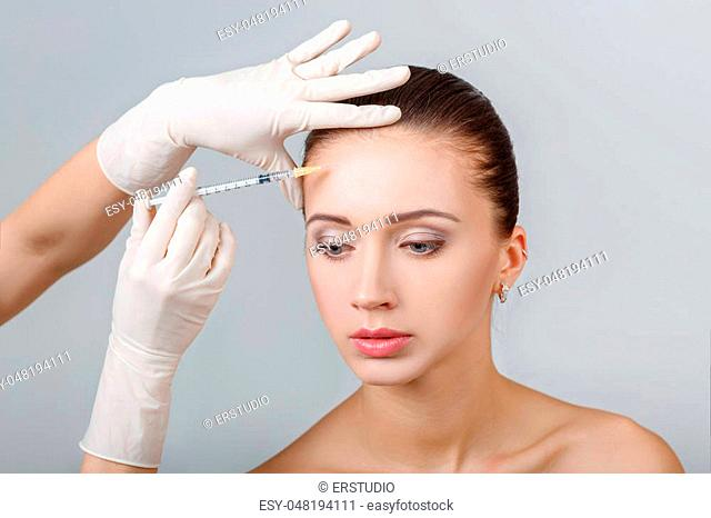 Portrait of young beautiful woman getting cosmetic lifting injection in forehead. Plastic Surgery. Cosmetic Treatment