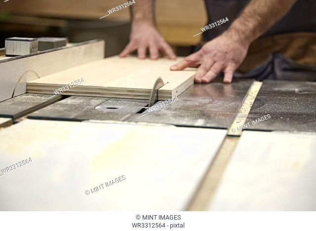 Carpenter using table saw in workshop
