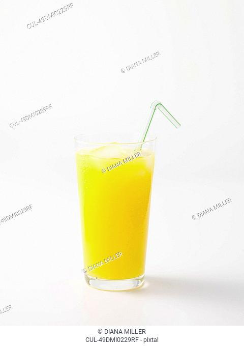 Straw in glass of orange juice