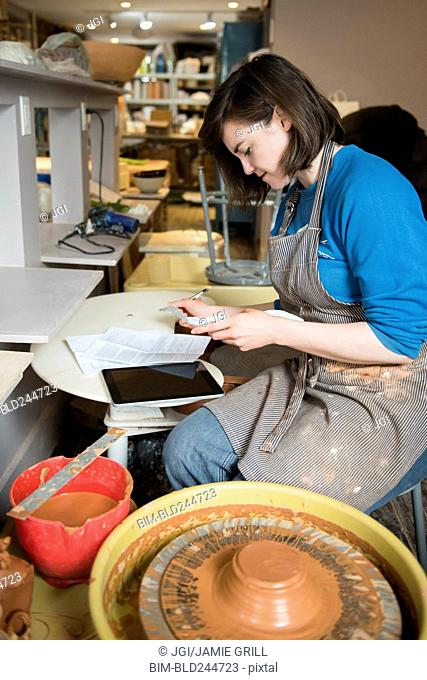 Caucasian woman reading paperwork near pottery wheel