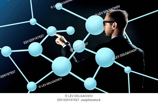 business, people, technology, science and biology concept - businessman in suit and glasses pointing finger to virtual molecule over black background
