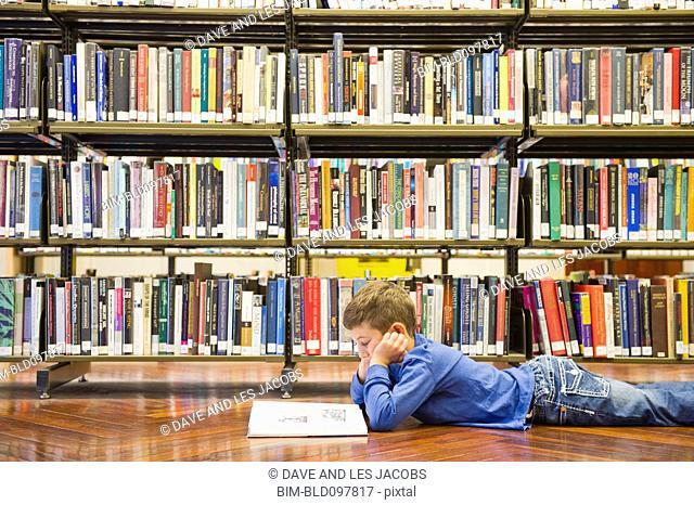Hispanic boy laying on library floor reading book