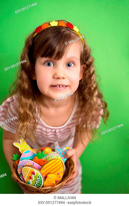 Portrait of a girl with a basket of Easter gingerbread cookies