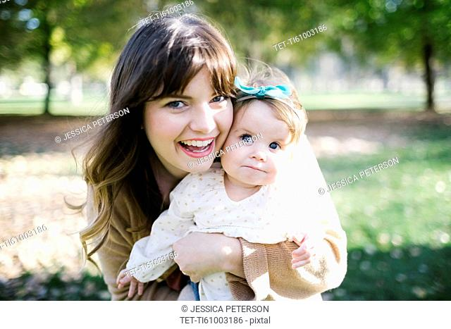 Portrait of mother carrying daughter (12-17 months) in park
