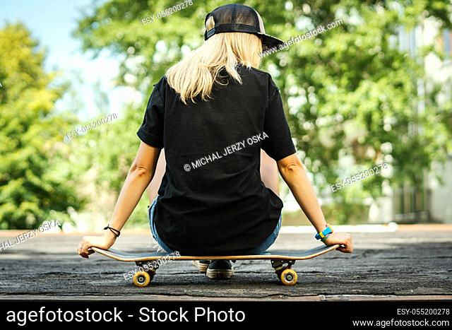 girl in a black T-shirt is sitting with her back on a skateboard and looks around