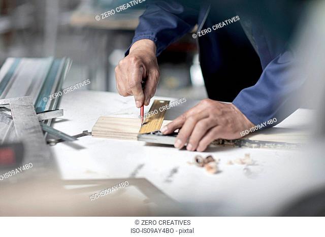 Hands of carpenter measuring angle wood on workshop bench