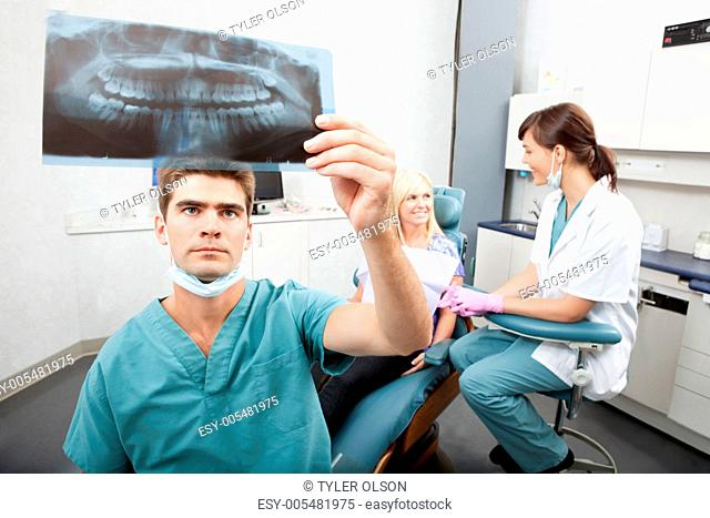 Dentist checking x-ray with assistant and patient in the background