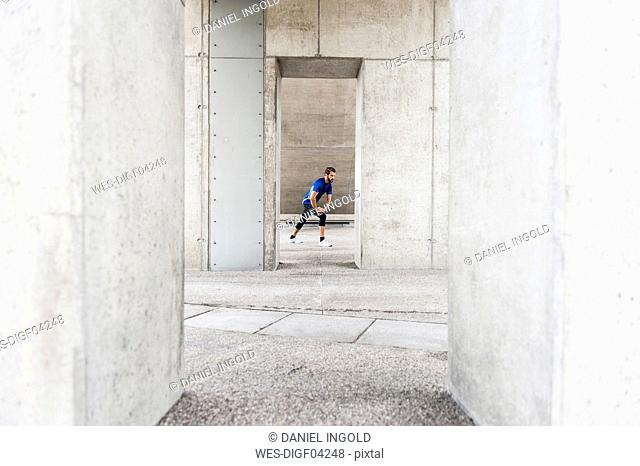 Man stetching at an underpass