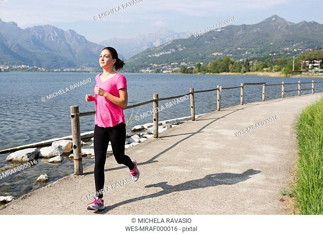 Italy, Lecco, young woman running along the lake