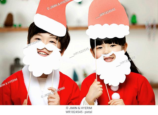 A boy and a girl dressed as Santa