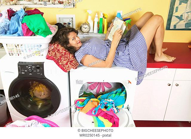 Woman reading while doing laundry
