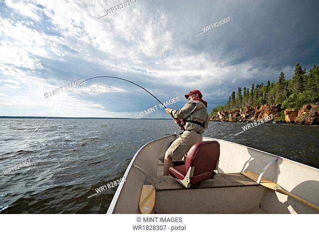 A man fishing from an open boat offshore. A fish on the line. The fishing rod bending from the weight