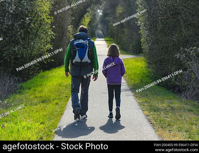 """04 April 2020, Brandenburg, Lietzen: A man and a girl are walking along a cycle path in the """"""""Lietzener Mühlental"""""""". The nature reserve """"""""Lietzener Mühlental""""""""..."""