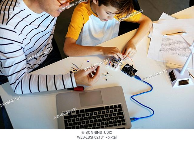 Father and son assembling a construction kit with laptop and wind turbine model