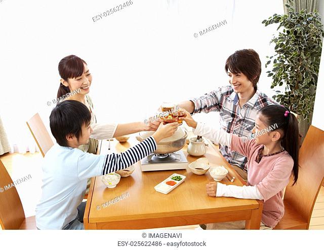 Parents and kids sitting around Japanese hot pot