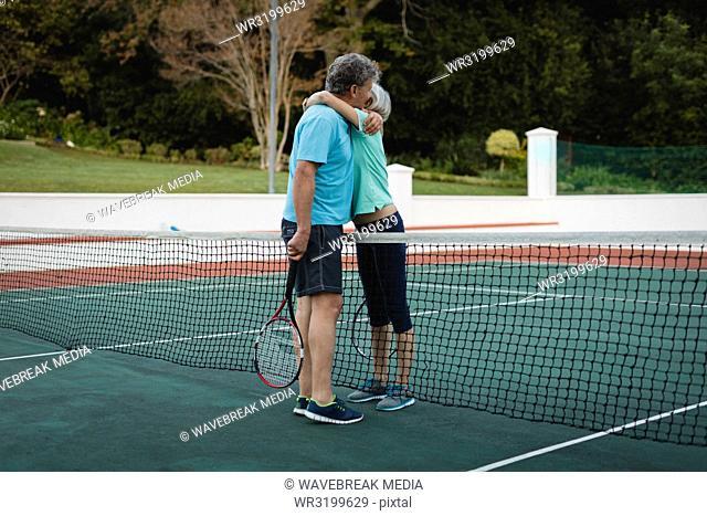 Senior couple hugging in tennis court