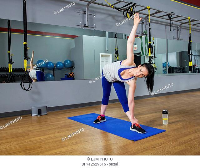 A fitness trainer doing a triangle yoga pose at a gym; Spruce Grove, Alberta, Canada