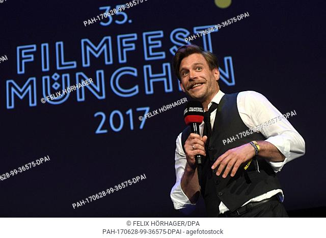 """Actor Ken Duken speaks on stage before the premiere of the film """"""""Berlin Falling"""""""", part of the Munich Film Festival, at the Gasteig cultural center in Munich"""