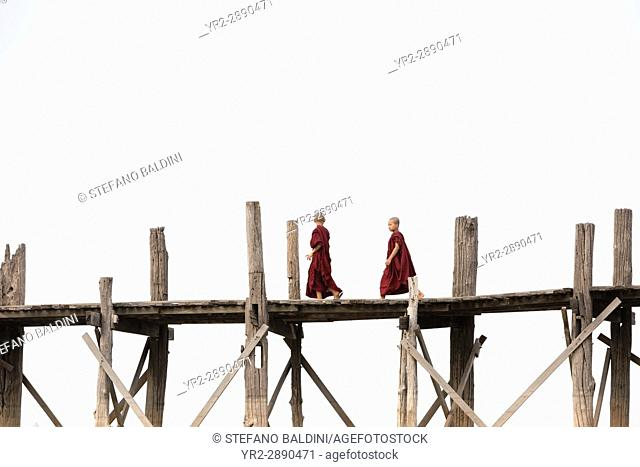 Monks crossing U Bein bridge, Amarapura's Taungmyo lake, Mandalay region, Myanmar