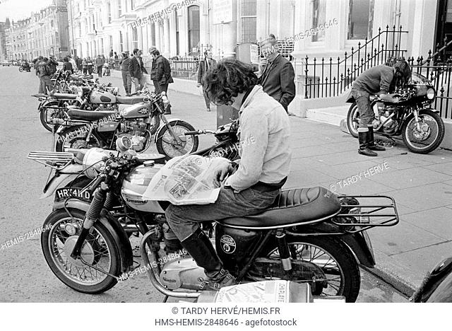 United Kingdom, Isle of Man, TT-1973, Tourist Trophy, Douglas, Central Promenade, couples form. Bikers are never far from their beloved