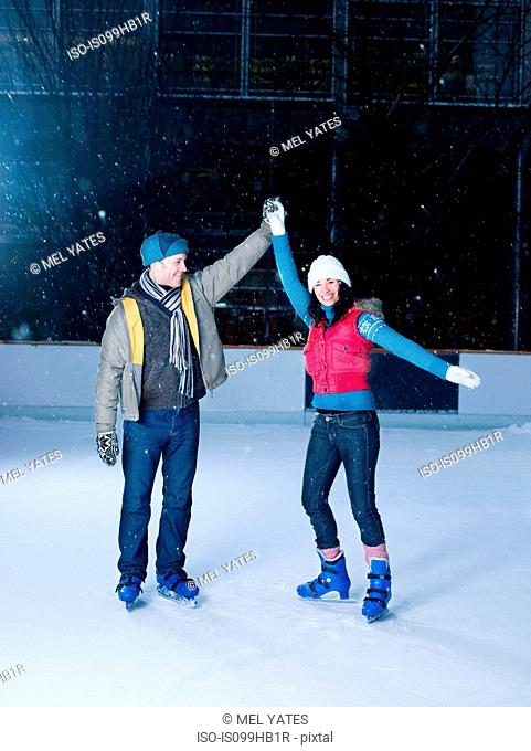 Couple holding hands on an ice rink