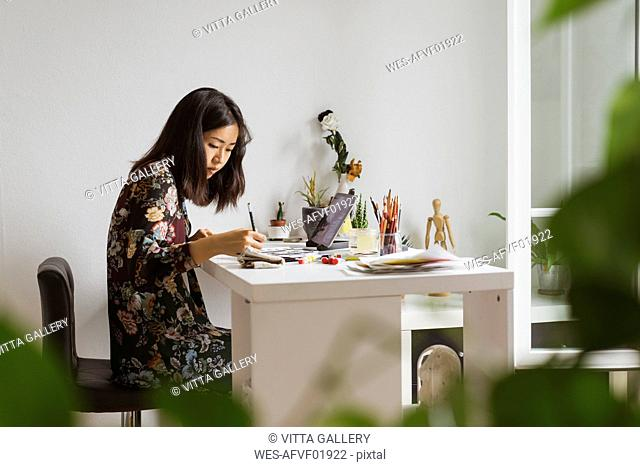 Illustrator sitting at work desk in atelier drawing