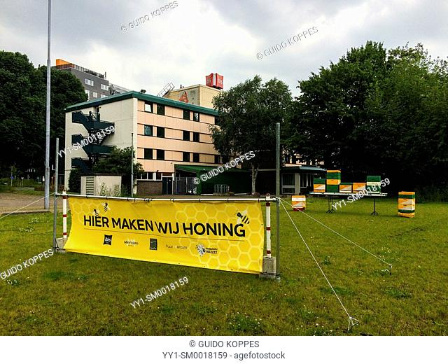 Tilburg, Netherlands. Beekeeper making honey on a field near an industrial estate hotel and telling about it with a banner