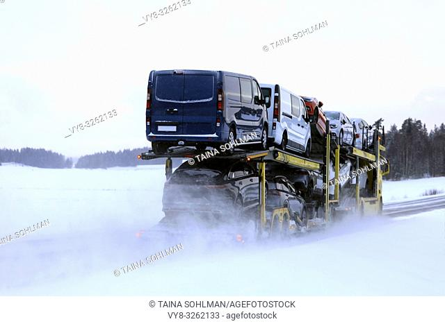 Car carrier truck transports a load of vehicles on a day of winter snowfall, rear view. Salo, Finland. January 18, 2019