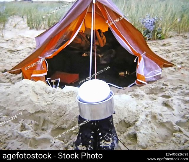 small tent at a beach with shoes and cooking pot