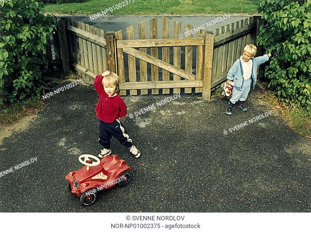 Two boys playing in front of a gate