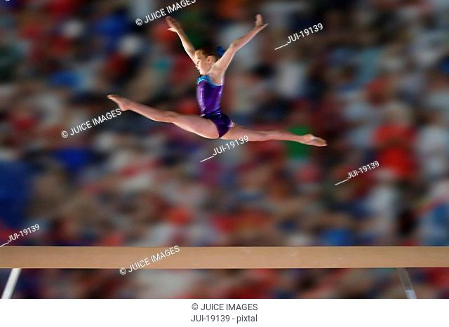 Young female 10-12 gymnast performing splits in air above balance beam, side view