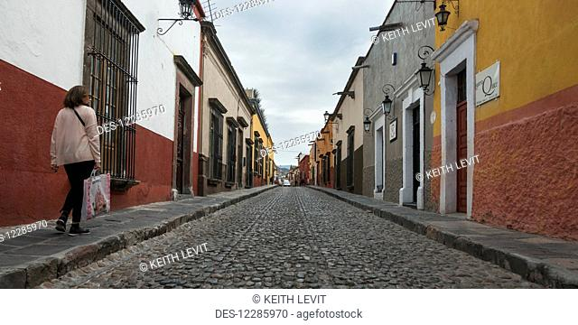 Pedestrian walking beside a cobblestone street and colourful buildings; San Miguel de Allende, Guanajuato, Mexico