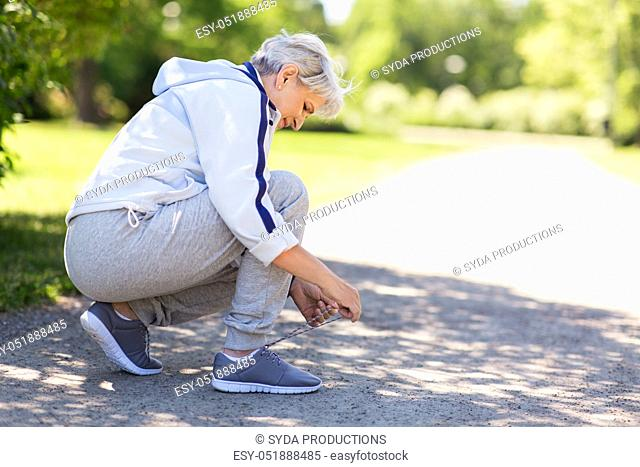senior woman tying sport shoe laces at summer park