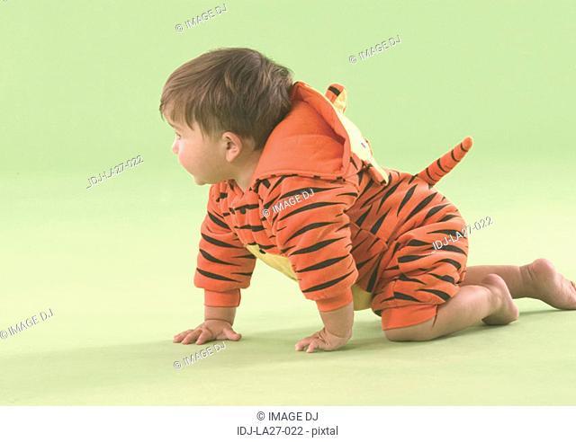 Side profile of a baby boy crawling