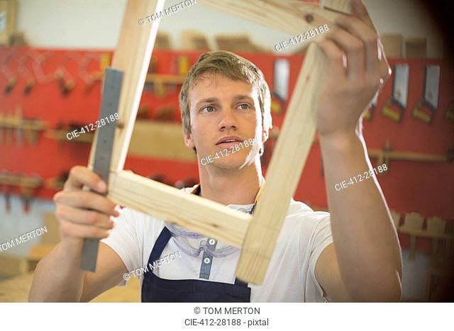 Carpenter examining wood in workshop
