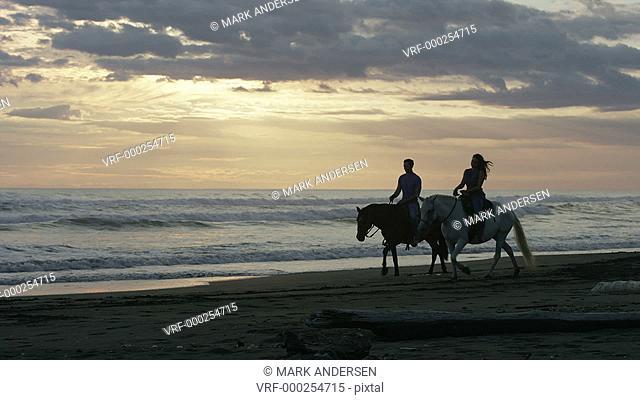Wide panning shot of couple riding horseback on beach / Esterillos, Puntarenas, Costa Rica