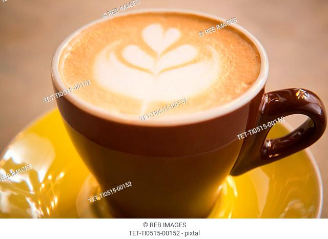 Coffee in yellow cup with heart shape